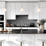 Modern Chic Kitchen White Barstools Grey Backsplash White Cabinet White Kitchen Island Black Countertops Undermount Sink Kitchen Pendants Flowers