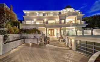 modern mansion exterior pavers home lighting fixtures railings wood framed glass doors glass windows garden garage door