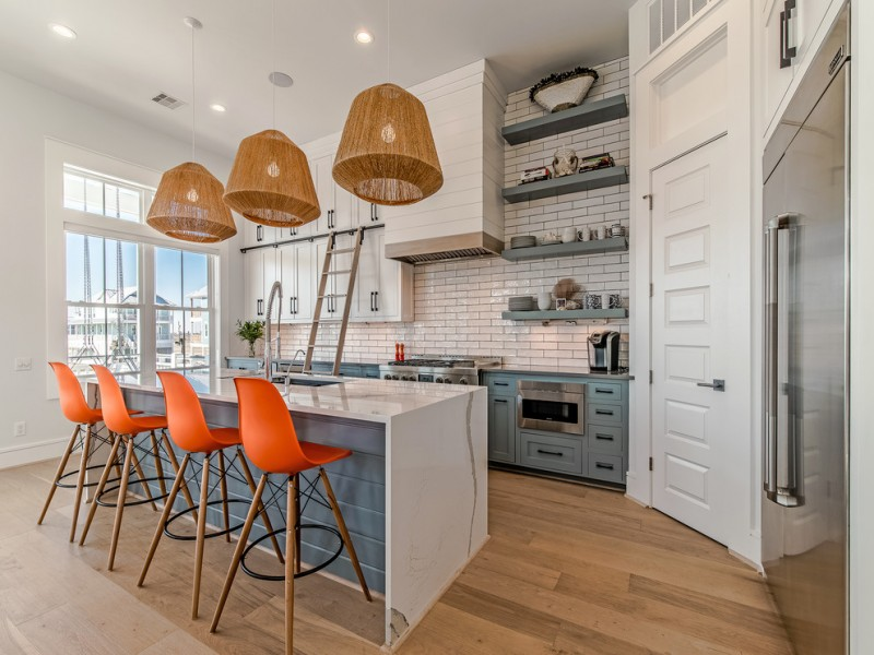 nautical kitchen unique pendants white kitchen cabinets white brick backsplash orange barstools granite coutertops wall shelves