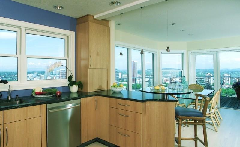 peninsular kitchen wood corner kitchen cabinet lazy susan windows recessed lightings, small pendants wood barstools with blue cushions