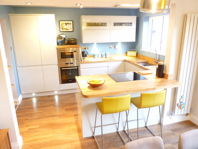 peninsular kitchen yellow barstools white kitchen cabinet wood countertop blue wall window recessed lighting undermount sink