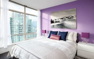 purple accent walls glass windows white curtains white bedding purple table lamos white nightstands area rug artwork purple and blue pillows