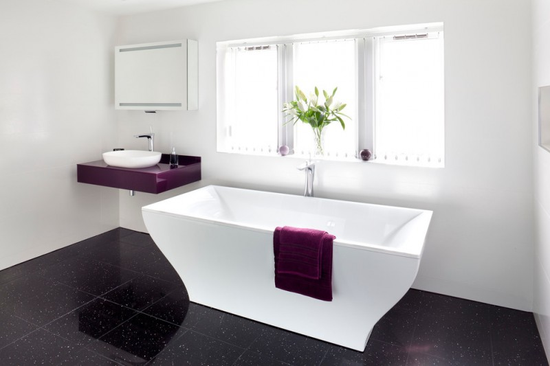 purple bathroom accessories purple hand soap bottle purple towel purple vanity white sink closed storage white freestanding tub windows