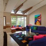Royal Blue Sofa Black Rug With Colorful Squares Pink Pillow Naguchi Table Corner Windows Corner Seating Space Artwork Mirror