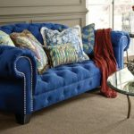 Royal Blue Sofa Tufted Sofa Beige Carpet Glass Coffee Table Glass Side Table Mirrored Side Table Patterned Pillows Brown Throw