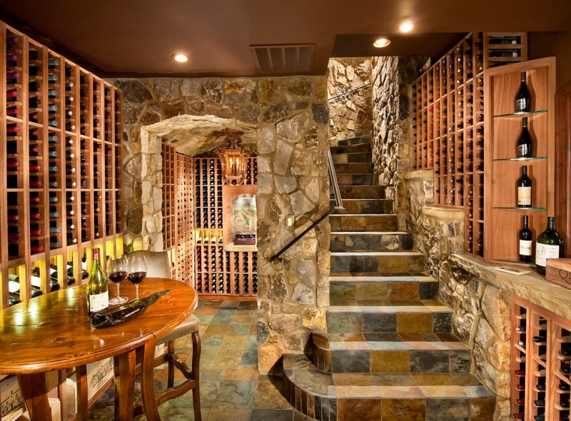 stone staircase stone wall slate floor wooden racks rounded table bar stool open shelving
