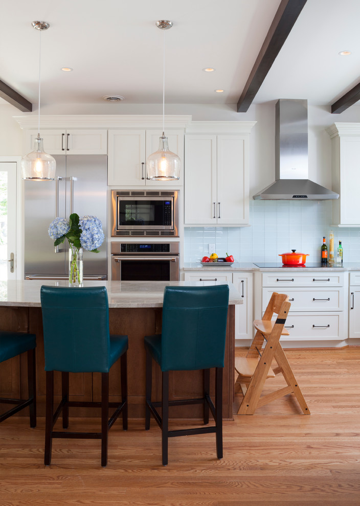 teal and brown barstools wood flooring white kitchen cabinets wood kitchen island with white countertop wood beams pendants