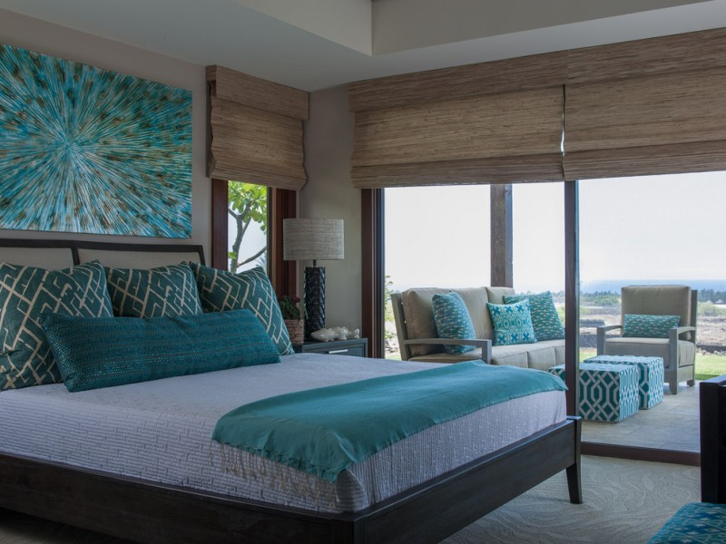 teal and brown master bed glass floor to ceiling windows woven shades artwork table lamp armchair sofa pillows barstools