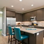 Teal And Brown Teal Barstools Brown Kitchen Cabinets And Island Beige Marble Countertops Wood Flooring Undermount Sink Beige Backsplash