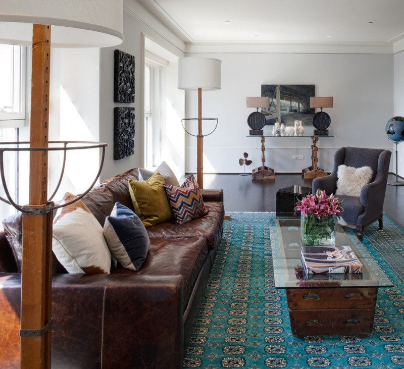 teal and brown teal rug brown leathered sofa wood coffee table with glass top armchair pillows table lamps gloor lamps windows