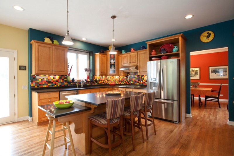 teal and brown teal wall brown kitchen cabinets and island black countertops island pendants barstools colorful backsplash