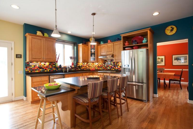 teal and brown teal wall brown kitchen cabinets and island black countertops island pendants barstools colorful backsplash