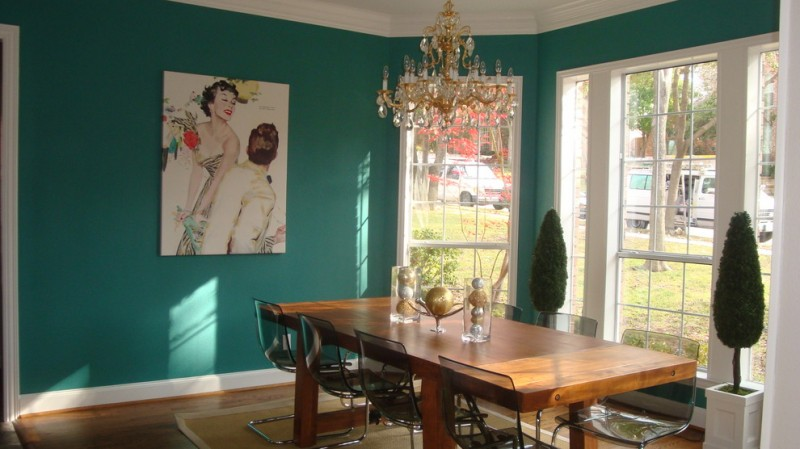 teal room teall wall chandelier wood dining table dining chairs indoor plant white framed glass doors and windows artwork