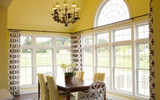 yellow dining room yellow classic chandelier yellow walls and ceiling white framed windows wood dining table yellow and white chairs curtains