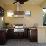 Beige Wall Dark Wood Cabinet Granite Countertop Stainless Steel Appliance Stainless Steel Hood TV Brick Floor Fan