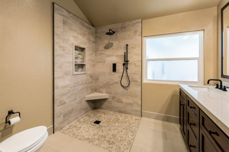 beige wall stone floor built in toilet corner seat shower tiled wall drop in sink dark wood cabinet