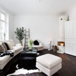 Black And White Living Room Furniture Cowhide Rug White Sofa Armchair And Ottoman Black Coffee Table Indoor Plant Corner Fireplace