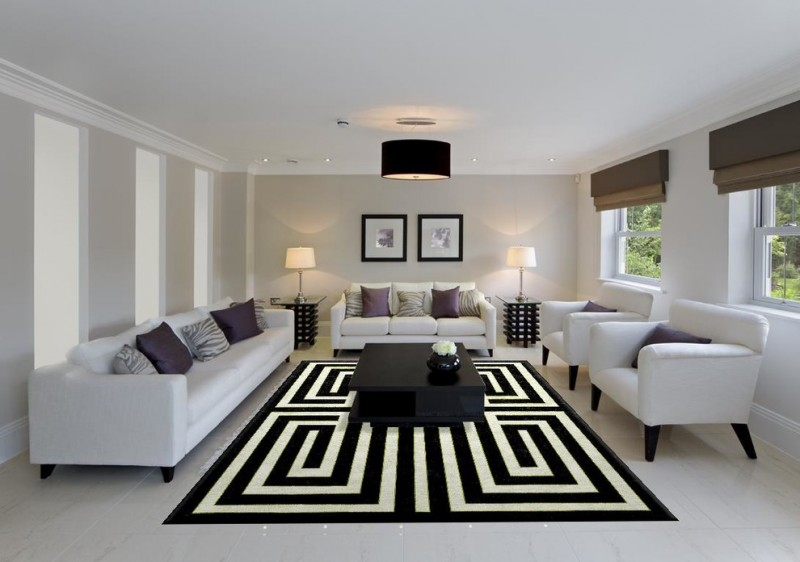 black white area rug black coffee table white sofa and armchairs purple pillows black ceiling lamp table lamps windows roman shades
