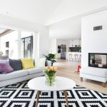 Black White Area Rug Colorful Pillows Grey Sofa White Coffee Table Glass Sliding Door With White Frames Small Bench Fireplace