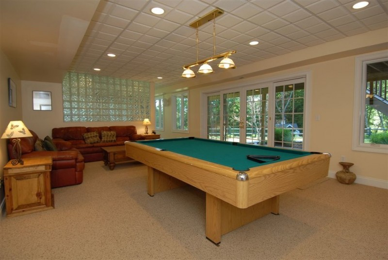 carpeted room tan leather sofa pool table pendant lights table lamp recessed lights frosted glass wall glass door white trim white ceiling