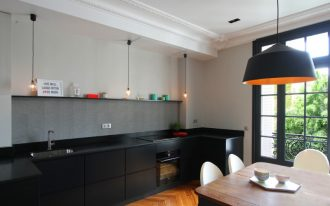 flat panel cabinet dark cabinet gray backsplash black countertop drop in sink floating shelf wooden dining table pendant lights