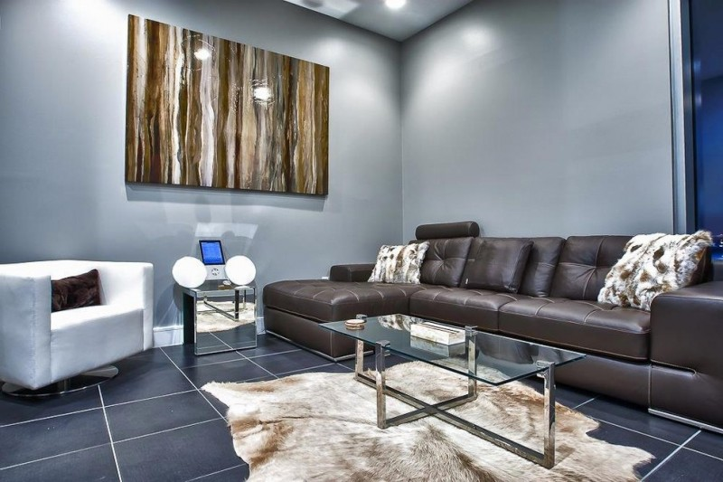 gray and brown living room brown leathered couch gray walls artwork white armchair glass coffee table grey floor shag rug