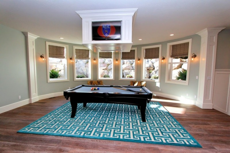 grey wall multiple window 4 way television media room pool table rug area wooden floor wooden chair wall lamps