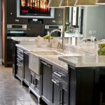 Kitchen Islands With Sinks And Dishwashers Golden Hanging Lamps White Marble Countertops Dark Cabinets And Island Barstools