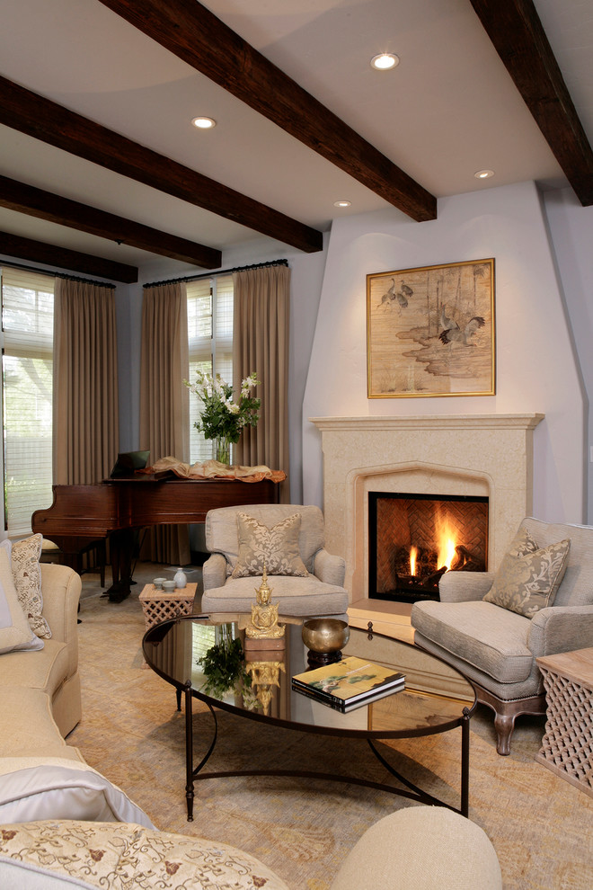 mirror tables for living room oval cocktail table ceiling wood beams beige curtains sofa armchairs fireplace artwork carpet