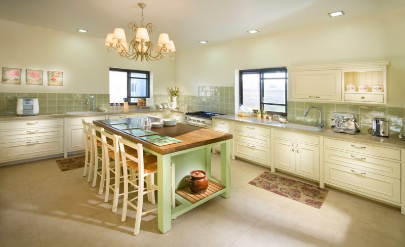 pastel kitchen green island green backsplash wood top chandelier shabby artwork windows with black frames barstools