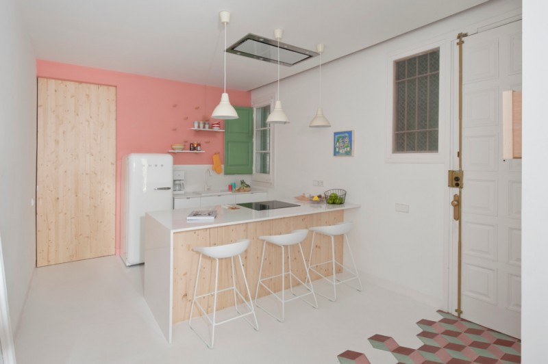 pastel kitchen pink wall green door accent window white walls and ceiling white countertop white barstools pendants