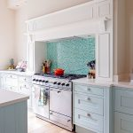 Pastel Kitchen Pink Wall Wood Flooring Blue Cabinets Blue And Green Mosaic Backsplash White Countertop Wood Flooring