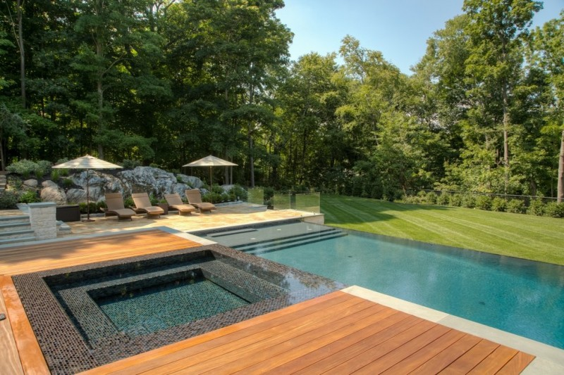 rectangular pool rectangulat hot tub spa wood deck mosaice tiled edge pool benches outdoor space rocks