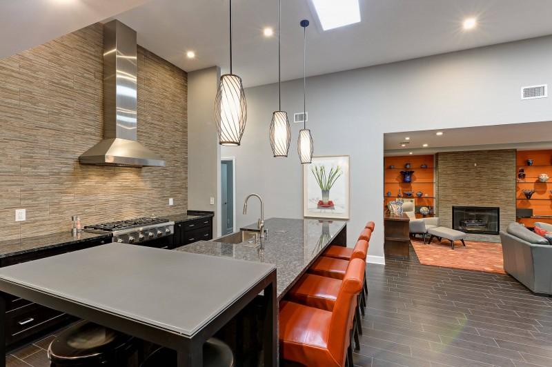 slate backsplash stainless stell hood granite countertop pendant lights red bar stools black cabinet undermount sink tiled floor