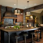 Slate Backsplash Tiled Backsplash Dark Wood Cabinet Brown Granite Countertop Island Bar Stool Hood Drum Lights Eat In Space Brick Fireplace Pendant Lights Dark Wood Floor