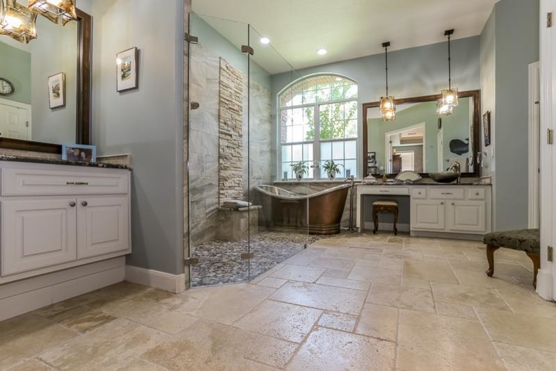 stone floor slate wall blue wall white cabinet mirror freestanding tub pendant lights vessel sink glass door granite countertop arched window