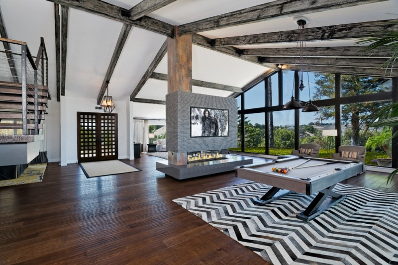 x leg pool table rug area wood floor two way fireplace built in TV white wall full height glass window pendant lights exposed beams