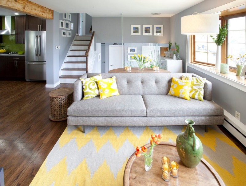 yellow and grey decoration area rug grey sofa coffee table yellow pillows staircase windows grey walls floor lamp wood flooring