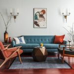 70's Furniture Artwork Blue Tufted Sofa Grey Area Rug Red And Grey Wooden Armchairs Coffee Table Wall Sconces Side Table