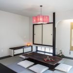 Asian Dining Table Pink Ceiling Light Asian Wall Decoration White Floor Cushions Wooden Dining Table Floor Hole Small Cabinet Windows Area Rug