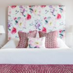 Floral Headboard White Bedding Red Throw Pillows White Wall Nightstands White Table Lamp White Curtain Pink Window Shade