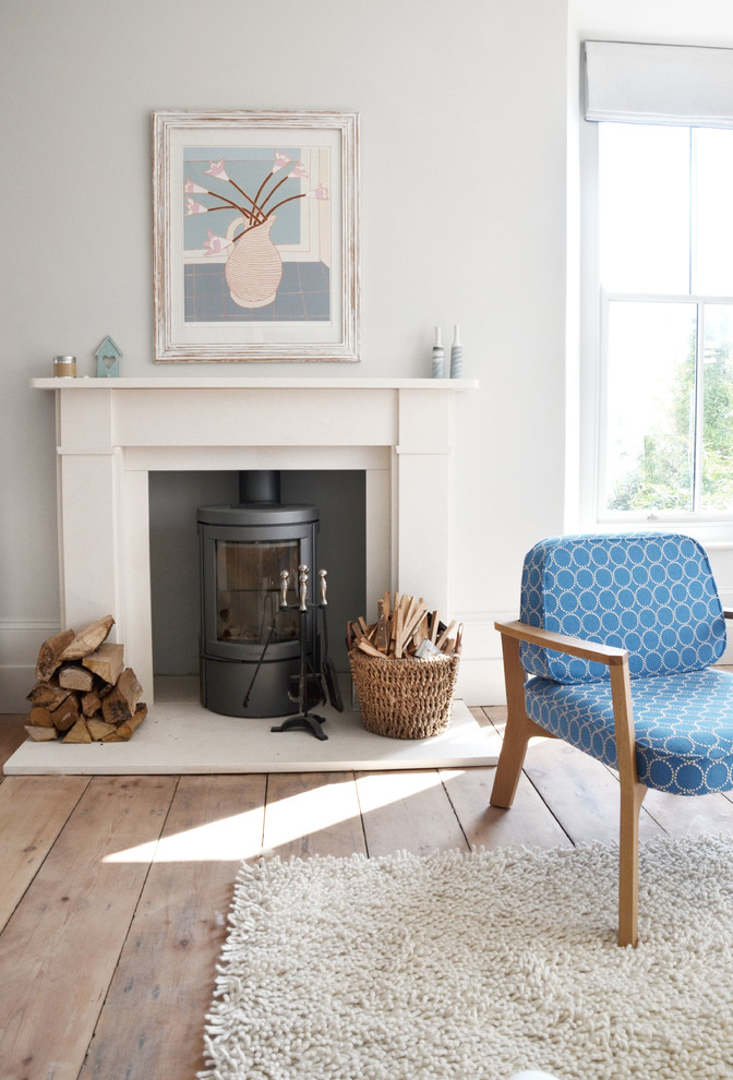 freestanding wood burning fireplace shag area rug blue patterned cushion minimalist armchair wood basket artwork fireplace mantel