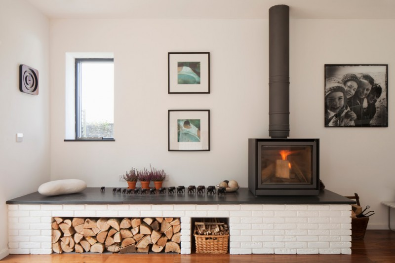 freestanding wood burning fireplace wood fire storage rattan basket white wall small windows black and white picture