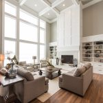 Full Height Glass Window Gray Sofa Coffee Table Rug Area High Ceiling White Wood Panel Fireplace Medum Tone Wooden Floor Open Shelves