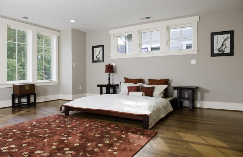 gray wall medium tone wooden floor rug area dark baseboard low bed side table windows white window trim wall decoration
