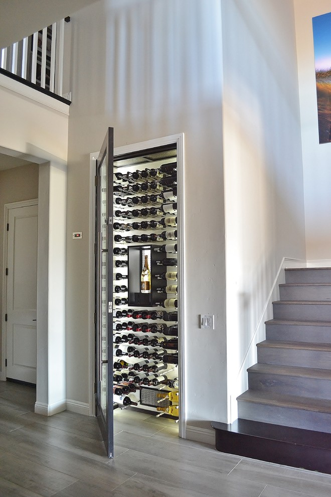 modern wine cellar white walls railing stairs wooden floor black framed wine cellar door glass door wine rack artwork