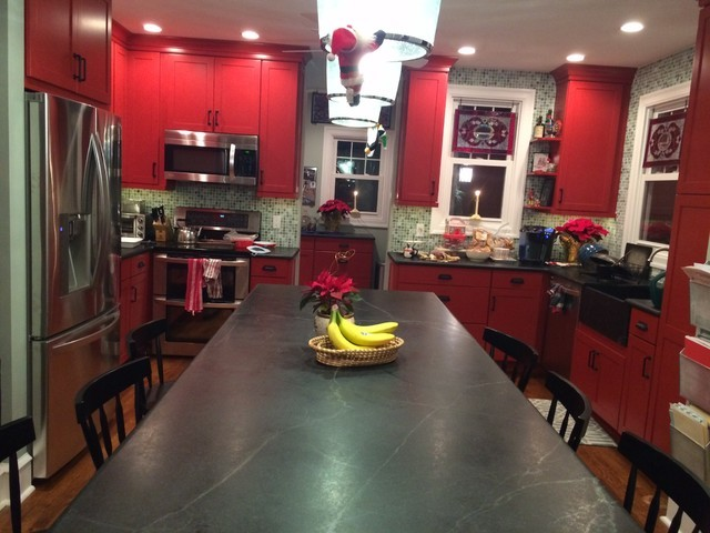 red and black kitchen red cabinets black countertop black table chairs pendant lamp black sink black hardware stove oven fridge