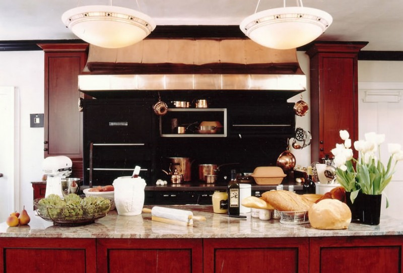 red and black kitchen res island red cabinets stovetop black countertop black appliances shelves pendan lamps oven