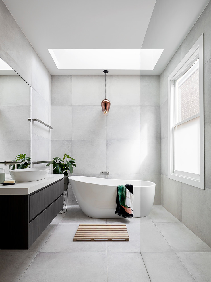 skylight golden light pendant light tiled wall tiled floor freestanding tub glass siding floating cabinet dark cabinet vessel sink window