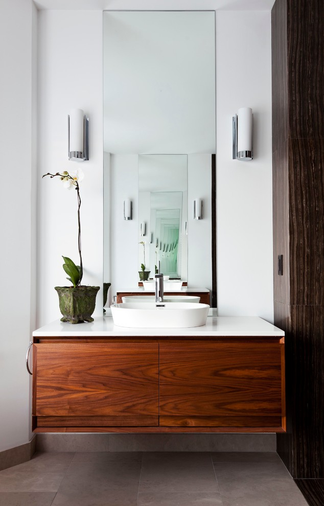 bathroom vanity refacing wall sconce wooden floating vanity white top white sink white walls mirror beige floor